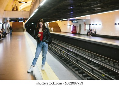 Young casual female waiting for train in metro station, using mobile phone