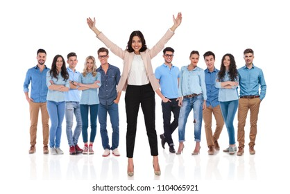 young casual group with their excited businesswoman leader celebrating with both hands in the air in front of them while standing on white background