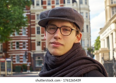 Young casual handsome guy wearing brown glasses and a trendy gray ivy flat cap, glancing amused to the camera in an urban setting in London city.