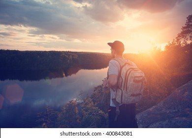 Young casual man with backpack and cap on the cliff above river and looking far away (intentional sun glare and lens flare)