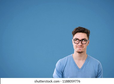 Young casual man in glasses looking up wonder making plan on bright blue background