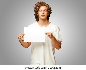 Young Casual Man Holding A Blank Message Isolated On Grey Background