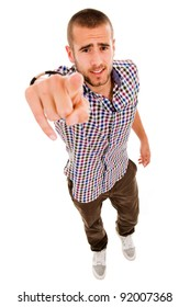 Young casual man pointing with finger at you, isolated on white