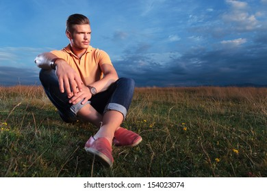 young casual man sitting outdoor in the grass and looking away from the camera while holding his feet crossed