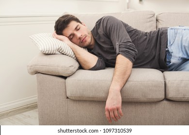 Young casual man sleeping on couch at home during day time