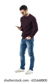 Young casual man with sunglasses typing text message on mobile phone. Full body length portrait isolated over white studio background.