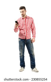 Young casual man using smart phone. Full body length portrait isolated over white background.