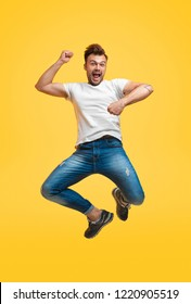 Young casual man in white t-shirt and jeans having fun and jumping high on yellow background looking at camera