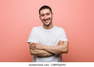Young casual man who feels confident, crossing arms with determination.