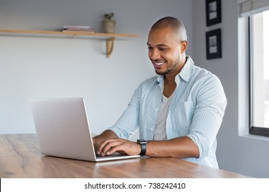 Young casual man working on laptop at home. African businessman typing on computer to send an email. Happy smiling black man surfing the net in a living room.