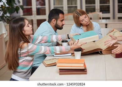 Young casual multiethnic people, muslim Arabian and African guys and caucasian girls, students preparing for exams, reading big thick books and sharing opinions. Co-working and education concept