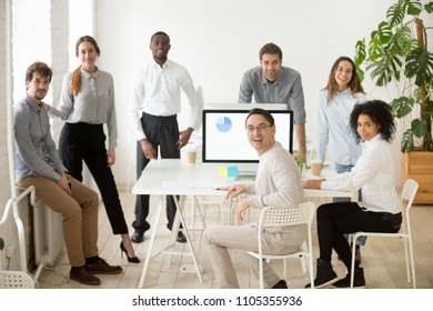 Young casual multiracial team and middle aged leader or coach looking at camera, smiling, standing near office desks in coworking space, posing for company business portrait. Team spirit, cooperation