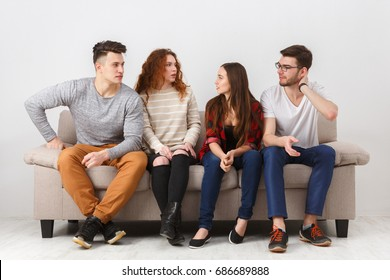 Young casual people, cheerful friends talking, having fun, sitting on couch indoors and laughing