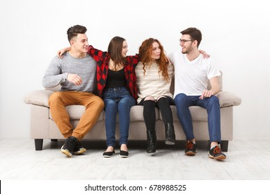 Young casual people communication, friends talking, having fun, sitting on couch indoors and laughing