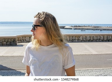 Young casual sporty dressed blonde woman with sunglasses in white t-shirt sits near street with ocean behind in Mallorca, Spain.