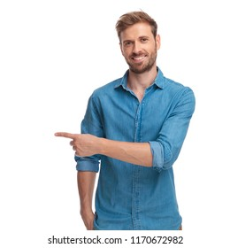 young casual studnt points finger to side on white background