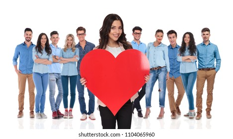 young casual team celebrating valentine's day with their businesswoman leader holding a red heart shape in front of them, standing on white background