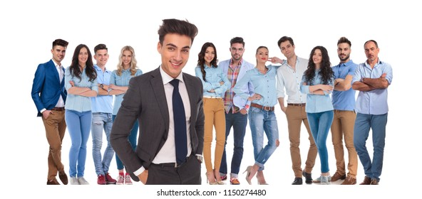 young casual team with relaxed businessman leader standing in front of them with hands in pockets, on white background