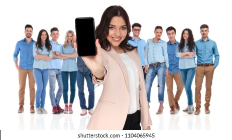 young casual team with smiling businesswoman leader showing blank telephone screen in front while standing on white background