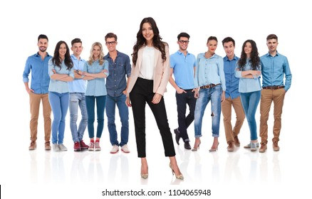 young casual team wearing blue shirts with businesswoman leader standing in front of them on white background