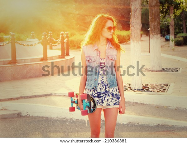 Young casual weared woman standing with skateboard in her hands. Redhair funky style women in trendy sunglasses standing alone outdoors backlit with her longboard in hands, looking away, toned image