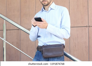Young casual wearing man with modern leather waist bag standing near office building and uses smartphone. Urban city lifestyle.