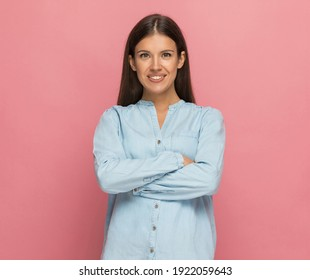 young casual woman crossing her arms at chest and smiling at the camera against pink background