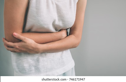 Young casual woman is having stomach ache.