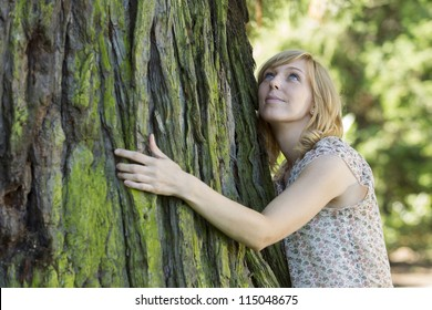 Young casual woman hugging large tree trunk as she looks up