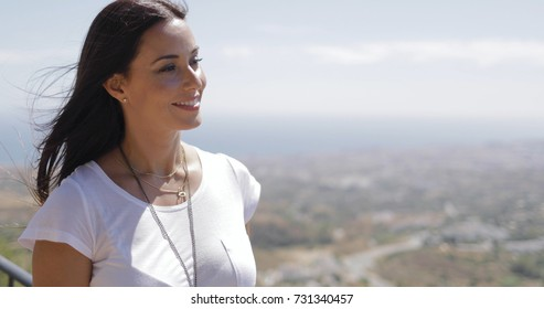 Young casual woman posing on observing point above city dreaming happily and looking away in sunlight.