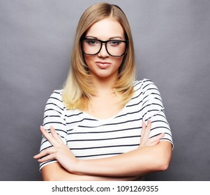 Young casual woman style over grey  background, studio portrait.