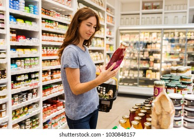 Young casual woman in a supermarket chose a bottle of fruit juice