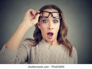 Young casual woman taking off eyeglasses and looking at camera with shock.