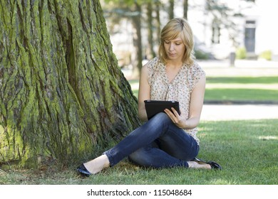 Young casual woman using digital tablet by tree on lawn