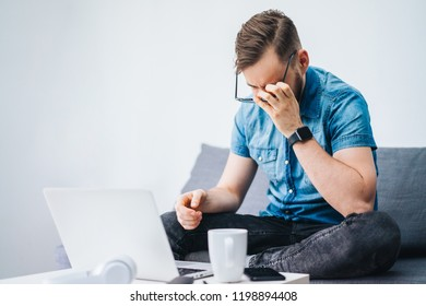 Young, casually dressed business man sitting on comfortable sofa looking exhausted after long working day. Blank white wall on the background. Copy space for your text.