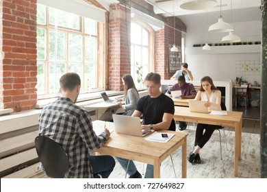 Young casually dressed employees at work in coworking office. Corporate team working on laptops and taking notes in shared room, brainstorming about new project, teamwork and collaboration concept.