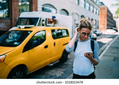 Young casually dressed female tourist walking on city street with smartphone using 4G connection, hipster girl browsing application on telephone for calling taxi making payment online while strolling