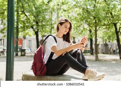 Young casually dressed girl using mobile phone in the park, pretty teenager taking picture or watching a video on modern gadget with wifi in public places in the fresh air during break in university