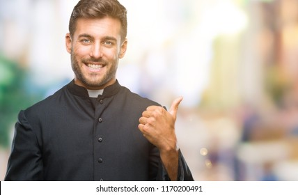 Young catholic christian priest man over isolated background smiling with happy face looking and pointing to the side with thumb up.