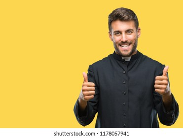 Young catholic christian priest man over isolated background success sign doing positive gesture with hand, thumbs up smiling and happy. Looking at the camera with cheerful expression, winner gesture.
