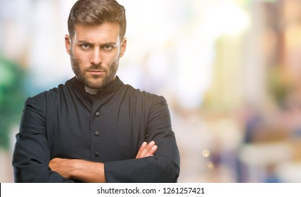 Young catholic christian priest man over isolated background skeptic and nervous, disapproving expression on face with crossed arms. Negative person.