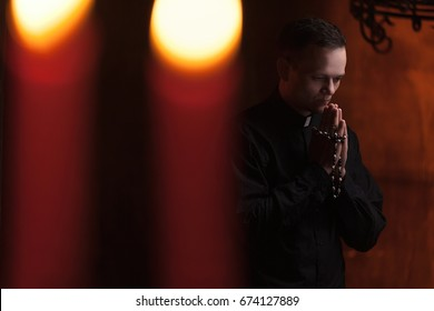 Young Catholic Praying priest. Portrait of priest Next to the candles prays with his hands folded near the face. Red wall on the background. Indoor handsome portrait of religion man