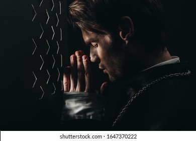 young catholic priest praying with closed eyes near confessional grille in dark with rays of light