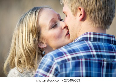 Young caucasian adult couple kissing outside in daytime