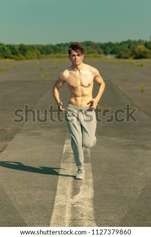 A young caucasian adult male jogging shirtless on a warm summer's day