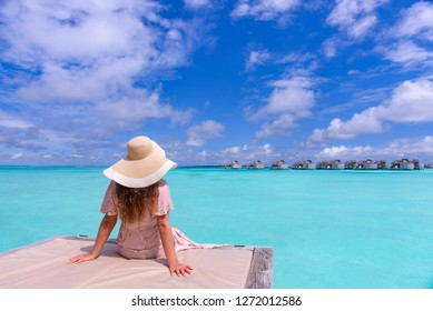 Young caucasian adult woman sitting on a sun bed against beautiful turquoise sea view. Wearing a hat and sea side suit.