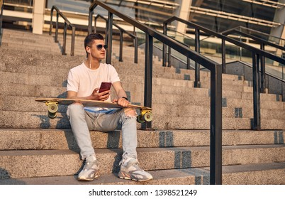 Young Caucasian American guy in glasses, sitting on the steps with a longboard on his knees, against the background of the city building on a warm summer sunny day, listening  music with headphones.