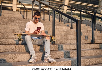 Young Caucasian American guy in glasses, sitting on the steps with a longboard on his knees, against the background of the city building on a warm summer sunny day, with a phone in his hand.