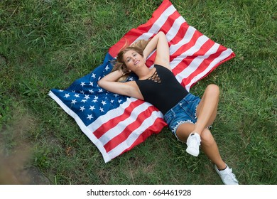 Young caucasian american woman resting on grass with american flag