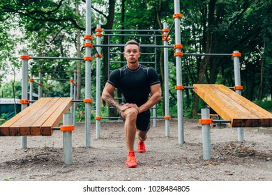 Young caucasian athlete in black sportwear and tattoos, training outdoor and posing